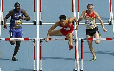 Liu Xiang of China clears a hurdle next to Willi Mathiszik of Germany and Ryan Brathwaite of Barbados in Daegu