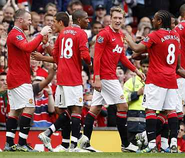 Manchester United players celebrate after scoring a goal against Arsenal