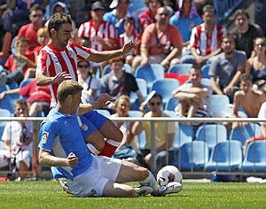 Atletico Madrid's Adrian Lopez and Osasuna's Sergio Fernandez (bottom) fight for possession during their La Liga match on Sunday