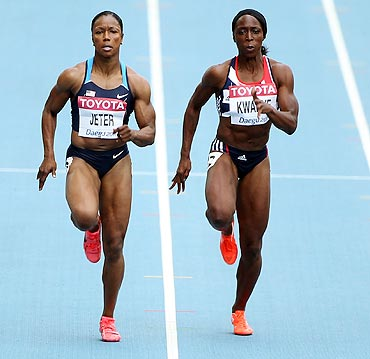 Carmelita Jeter of United States and Jeanette Kwakye of Great Britain compete in the women's 100 metres heats on Sunday