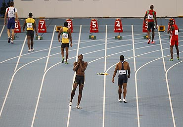 Usain Bolt (centre) of Jamaica reacts after being disqualified for a false start
