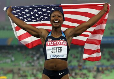 Carmelita Jeter of United States celebrates with her country's flag after the women's 100 metres final