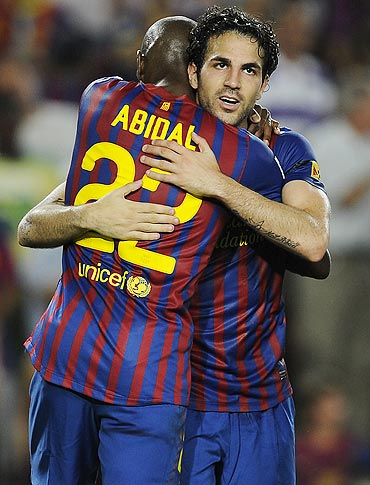 Cesc Fabregas celebrates with his teammate Eric Abidal after scoring