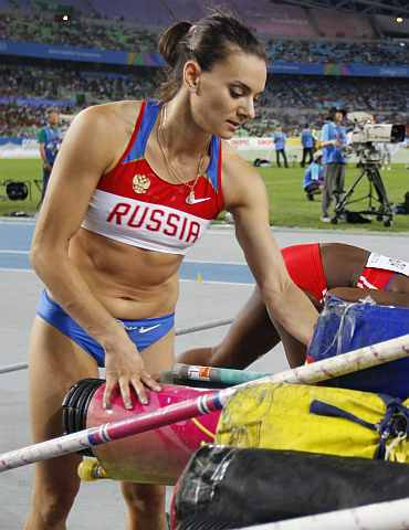 Yelena Isinbayeva packs her equipment after failing to progess in the women's pole vault final