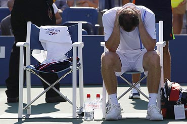 Conor Niland sits after retiring from the match against Novak Djokovic