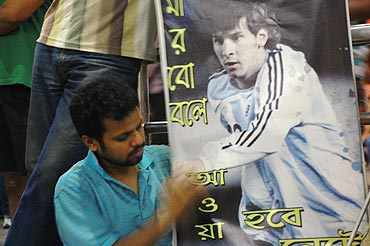 A Messi fan holds up a Messi poster outside the Kolkata airport