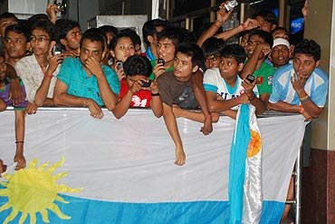 Fans hold up Argentina's national flag as they await the arrival of Lionel Messi at Kolkata airport