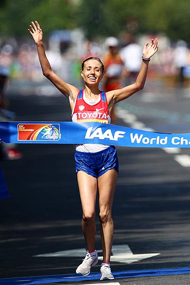 Gold medalist Olga Kaniskina of Russia celebrates as she crosses the finish line