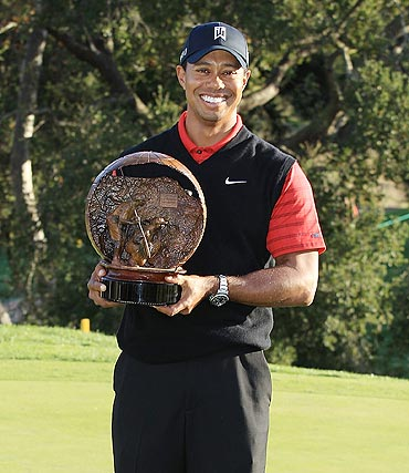 Tiger Woods poses with the trophy after winning the Chevron World Challenge
