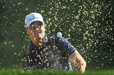 Zach Johnson plays a bunker shot on the 11th hole