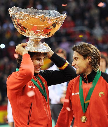 Rafael Nadal (left) of Spain holds the Davis Cup trophy as he celebrates with his team-mate David Ferrer