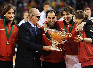 King Juan Carlos (left) of Spain holds the Davis Cup trophy with team captain Albert Costa (second left), Rafael Nadal (second right) and David Ferrer