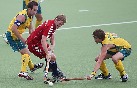 Ashley Jackson of Great Britain is challenged by Australia's Barry Middleton (left) and Edward Ockenden during their Champions Trophy match in Auckland on Monday