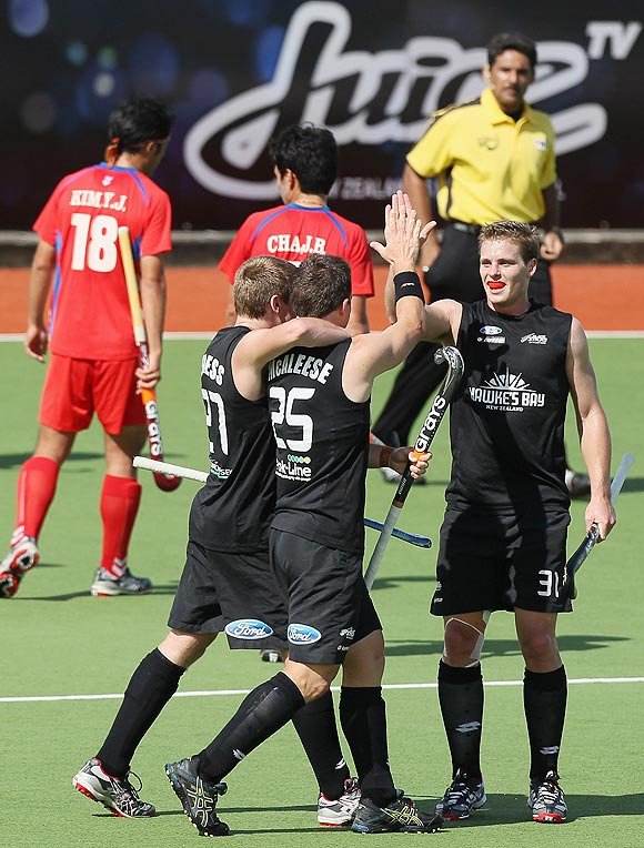 New Zealand's Shea McAleese celebrates with teammates Stephen Jenness and Steven Edwards after scoring against Korea during their Champions Trophy match in Auckland on Monday