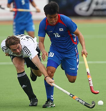 Sik Hyo You of Korea is challenged by Florian Fuchs of Germany (left)