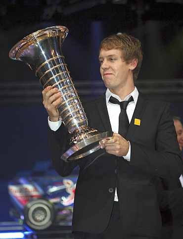 Formula One World Champion Sebastien Vettel of Germany holds his trophy during the 2010 FIA Prize Giving gala in Monaco