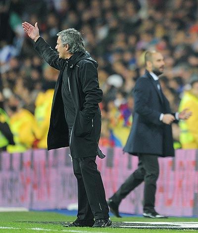 Head coach Jose Mourinho (left) of Real Madrid reacts beside coach Josep Guardiola of FC Barcelona