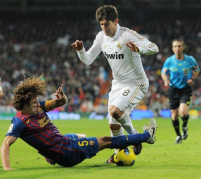 Carles Puyol (left) of FC Barcelona slides to stop Kaka of Real Madrid