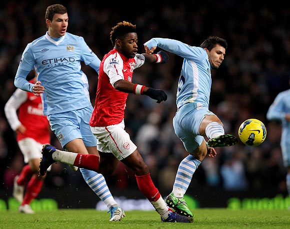 Arsenal's Alexandre Song challenges Manchester City's Sergio Aguero as they vie for possession