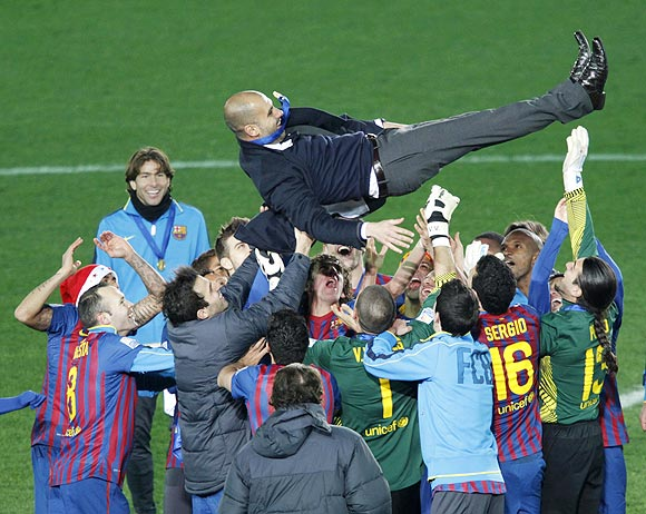 Barcelona players celebrate with coach Pep Guardiola after winning the Club World Cup