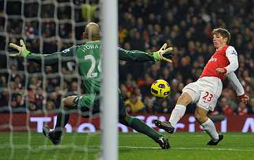 Andriy Arshavin scores past Tim Howard during their match at the Emirates
