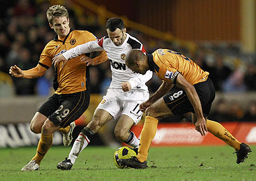 Wolverhampton Wanderers' Kevin Doyle (left) and Karl Henry (right) challenge Manchester United's Ryan Giggs