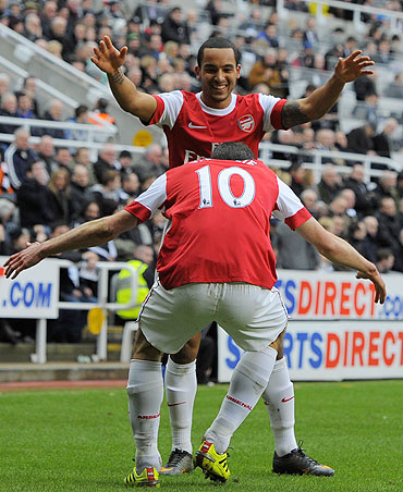 Arsenal's Robin Van Persie (10) celebrates with Theo Walcott after scoring against Newcastle United on Saturday