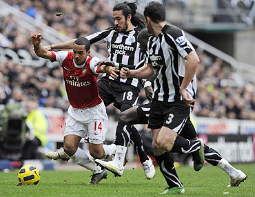 Arsenal's Theo Walcott (left) is challenged by Newcastle United's Jonas Gutierrez (2nd from left), Cheik Tiote (2nd from right) and Jose Enrique