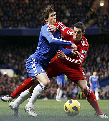Chelsea's Fernando Torres (left) and Liverpool's Daniel Agger get involved in a fierce challenge