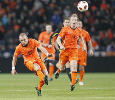 Wesley Sneijder of the Netherlands (L) shoots the ball, while teammate Dirk Kuyt watches, during their international friendly soccer match against Austria in Eindhoven