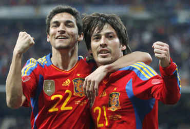 Spain's David Silva (R) celebrates with team mate Jesus Navas after scoring a goal against Colombia