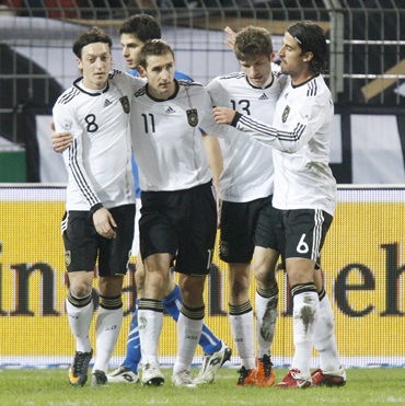 Germany's Miroslav Klose (2nd L) celebrates a goal against Italy with teammates Mesut Oezil (L), Thomas Muller (2nd R) and Sami Khedira (R) during their international friendly in Dortmund