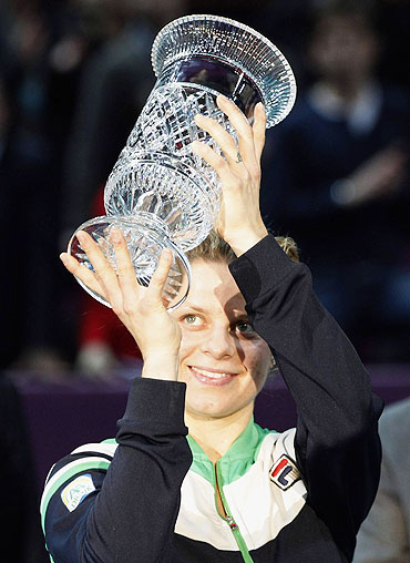 Kim Clijsters celebrates with the trophy after being declared WTA world number one after her Paris Open semi-final win against Jelena Dokic on Friday