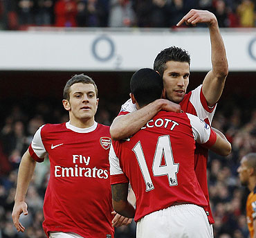 Arsenal's Robin Van Persie gestures as teammate Arsenal's Theo Walcott (14) congratulates him after scoring their second goal