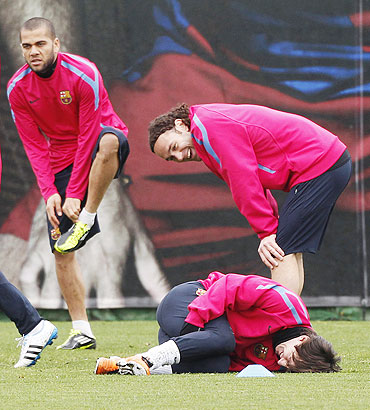 Barcelona's Lionel Messi (centre) jokes with teammates Diego Milito (right) and Dani Alves during a training session at Ciutat Esportiva Joan Gamper near Barcelona on Tuesday