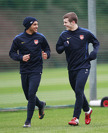 Arsenal's Theo Walcott (left) and Jack Wilshere attend a team training session in London Colney on Tuesday