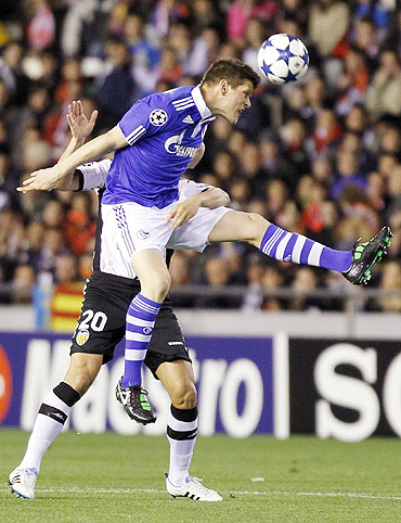 Schalke 04's Klaas-Jan Huntelaar (foreground) goes for an aerial ball  against Valencia's Ricardo Costa on Tuesday