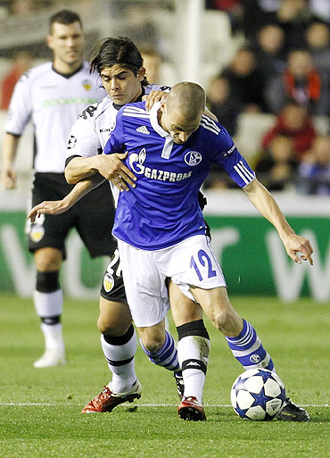 Schalke 04's Peer Kluge (front) is challenged by Valencia's Ever Banega on Tuesday