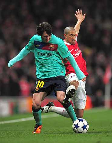 Arsenal's Gael Clichy challenges Barcelona's Lionel Messi during their Champions League match at the Emirates Stadium