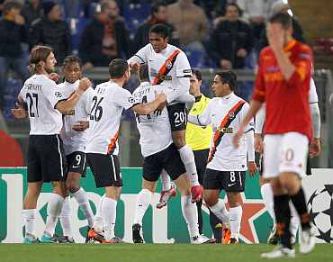 Shakhtar Donetsk players celebrate after scoring a goal during their match against AS Roma during their Champions League match at the Olympic stadium in Rome