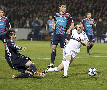 Real Madrid's Karim Benzema (C) shoots to score against Olympique Lyon during their Champions League match at Gerland stadium