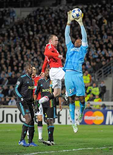 Marseille's Steve Mandanda claims the ball under a challenge by Wayne Rooney of Manchester United during the Champions League match