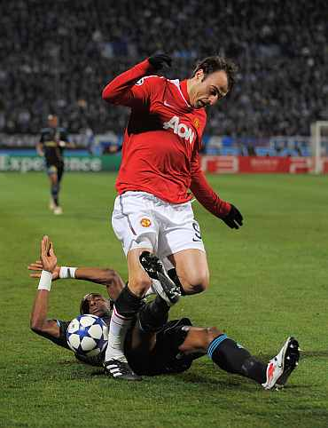 Dimitar Berbatov of Manchester United is challenged by Stephane Mbia of Marseille during the Champions League match