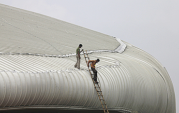 Workers climb down the roof of the weightlifting venue for the Commonwealth Games. A portion of the false ceiling at the venue caved in prior to the Games in September last year