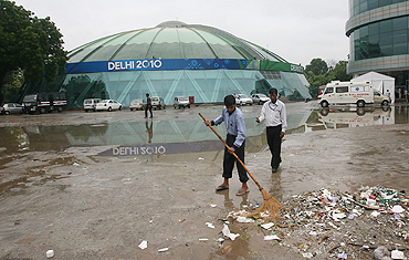 A sweeper sweeps outside the Talkatora Boxing Stadium in New Delhi