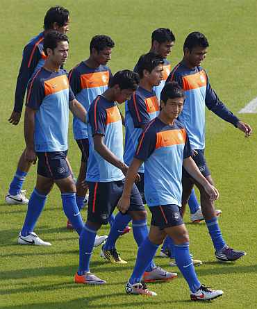 Indian players warm up during a practice session at Al Wakrah Stadium in Doha