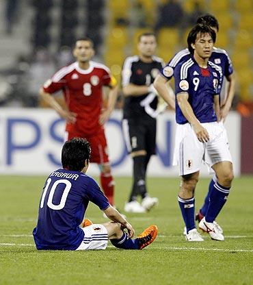 Japan and Jordan players react after their match on Sunday