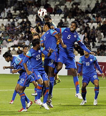 Indian players try to block a Tim Cahill header during their Asian Cup match against Australia on Monday