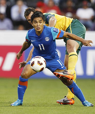 India's Sunil Chhetri holds off the challenge of Australia's Lucas Neill during their Asian Cup match on Monday