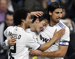 Real Madrid's Mesut Ozil (centre) is congratulated by team-mates Marcelo (left) and Sami Khedira after scoring the winner during their Spanish King's Cup quarter-final first leg against Atletico Madrid